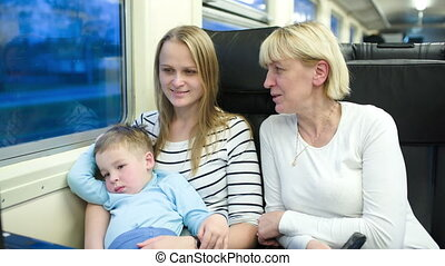Mother, son and grandmother traveling by train - Family of...