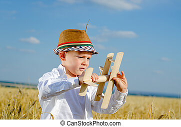 Serious little boy playing with a toy airplane