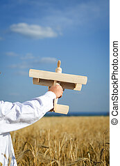 Little boy playing in farmland with a toy airplane holding...