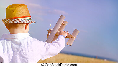 Little boy in a cute hat playing with an airplane