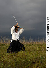 aikido - young aikido man with a sword outdoors