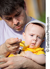 Father trying to feed infant a spoonful of baby food