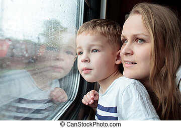 Mother and son looking through a train window as they enjoy...