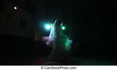 bride spinning at darkness in colored lights