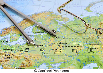Eyeglasses and a measuring instrument on a geographic map of...