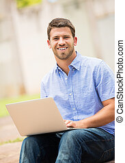 Young man working outside on laptop