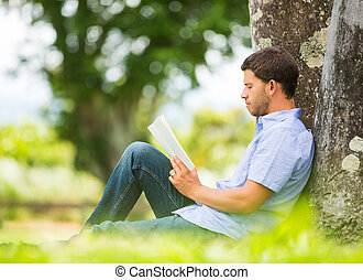 Man reading book in park, sitting under a tree. Relaxing...