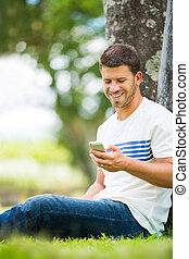 Young man using cell phone outside in park