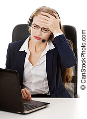 Business woman at call center is having headache. She's...