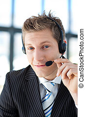 Young businessman with a headset on in a call center - Young...