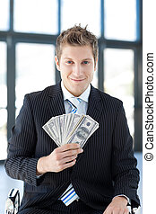 Smiling businessman holding money in office