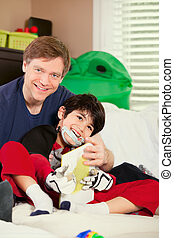 Handsome father playing cars with disabled son on floor mat