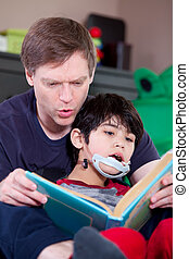 Father reading book to disabled little son - Father reading...