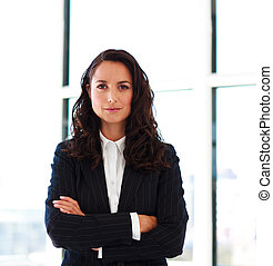 Confident businesswoman with folded arms in office