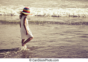 Sad little girl walking at the beach in the day time