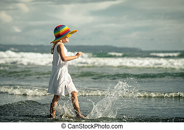 Happy little girl walking at the beach in the day time -...