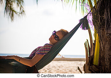 woman in sunglasses lying at hammock by the beach. Koh...