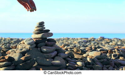 Hand putting last stone on pyramid at the seaside