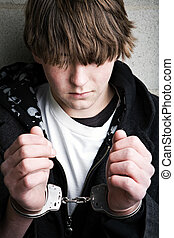 teen crime - kid in handcuffs - teen male portrait wearing...