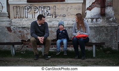 Parents and their child sitting on the bench near old grungy building