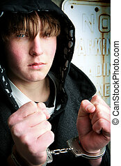 teenager in handcuffs closeup against a wall