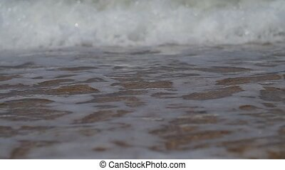 Close up of sea surf splashing on a pebble beach