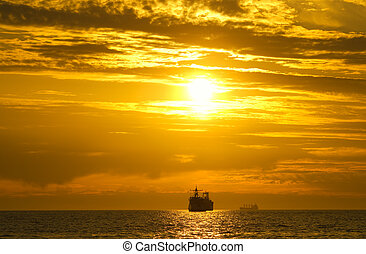 colorful sunset on the sea - Cargo ship sailing away against...