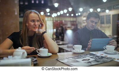 Young people in a cafe with phone and Tablet PC