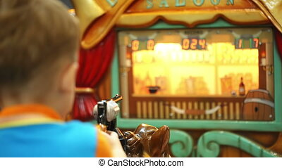 Boy riding a toy horse and shooting with toy gun - Back view...