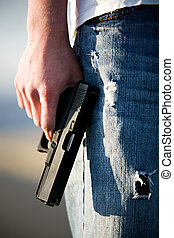 teen with handgun - Teen male holding modern 9mm handgun,...