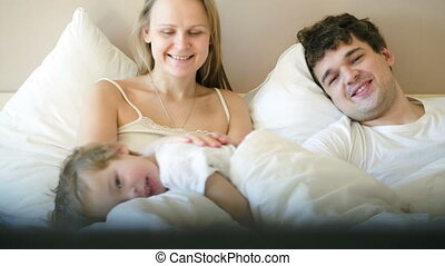 Happy family of three watching TV in the morning - Young...