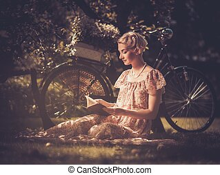 Blond retro woman with a book in summer dress sitting on a...