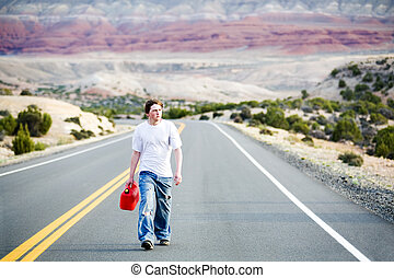 teenager out of gas, walking down rural mountain road with...