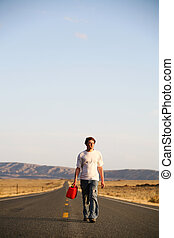 out of gas - male teenager walking down the highway with...