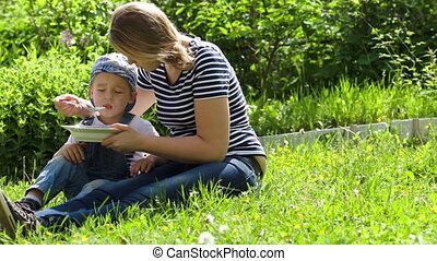 Mother feeding her son outdoor on a summer day