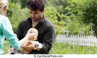 Parents feeding baby sitting on the grass
