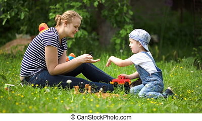 Mother and son playing outdoor on the green lawn - Young...
