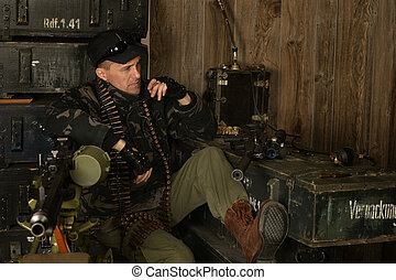 Armed combat soldier - Thoughtful armed soldier sits among...