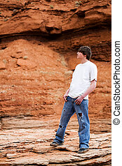 teenager male in mountains - teenager standing on a rock in...