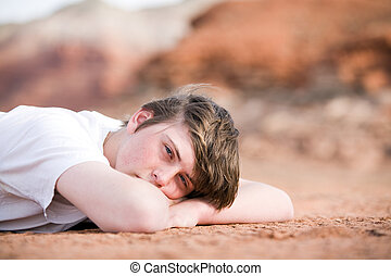 male teenager laying on ground - teenager male laying on the...