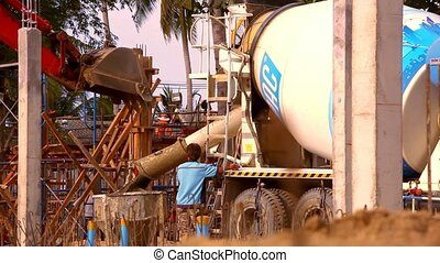 KOH SAMUI, THAILAND - JUNE 21: structure of concrete mixing and falls asleep in the concrete tank at construction site. Video