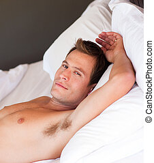 Portrait of a young man relaxing in bed