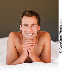 Young man relaxing in bed smiling at the camera