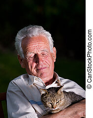 Old man with cat - Old man holding his cat in arms on dark...