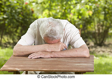 Taking a nap - Old man fall asleep with head on table in...