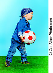playing football - Cute little boy playing football Fashion...