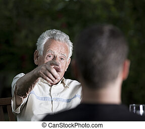 Accuse - Disappointed old man pointing forefinger in man in...