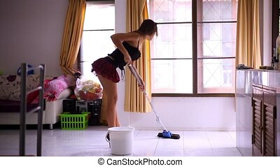 Beautiful young sexy maid cleans tiled floor, concept cleaning. Video