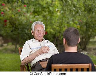 Chatting in garden - Old man talking with grandson in garden...