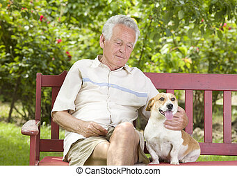 Senior man with his dog - Old man cuddling his dog on bench...